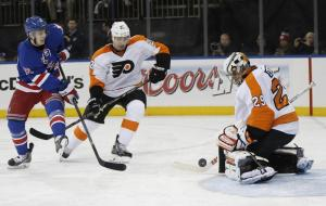 Ray Emery stops a shot with Jesper Fast searching for a rebound.  AP Photo/Kathy Willens