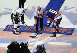 Islanders great Billy Smith drops the ceremonial first puck with John Tavares and Sidney Crosby at center ice. AP Photo by Kathy Kmonicek/Getty Images