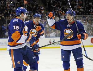 Ryan Strome celebrates a goal with teammates Brock Nelson and Travis Hamonic. AP Photo by Kathy Kmonicek/Getty Images