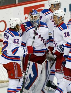 Metro Champs: Winning netminder Henrik Lundqvist gets congrats from Carl Hagelin (left) and Dominic Moore (right) after the Rangers clinched the Metro Division with a 3-2 win over the Wild Thursday night. AP Photo by Jim Mone/Getty Images