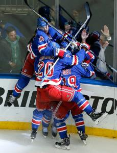 The New York Rangers celebrate their game winning overtime goal against the Washington Capitals in Game 7 of the Eastern Conference semifinals during the NHL hockey Stanley Cup playoffs, Wednesday, May 13, 2015, in New York. (AP Photo/Julie Jacobson)