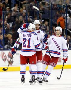 New York Rangers' Derek Stepan, left, is congratulated on his goal against the Columbus Blue Jackets by teammates Marc Staal, center, and Dan Girardi during the third period of an NHL hockey game Monday, April 4, 2016, in Columbus, Ohio. The Rangers beat the Blue Jackets 4-2. (AP Photo/Jay LaPrete)